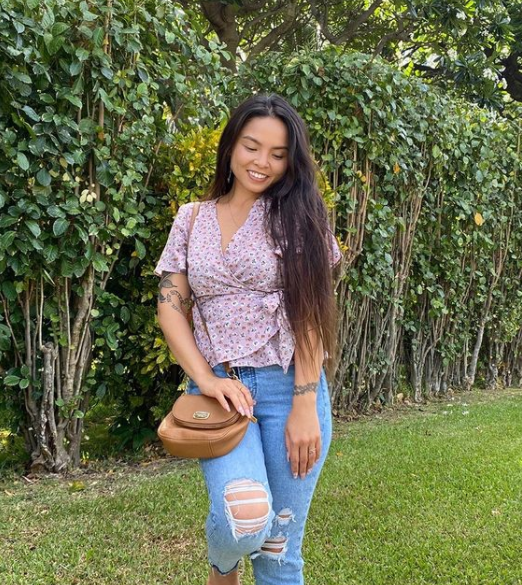 Girl standing in front of trees, with floral lavender purple wrap blouse and distressed jeans with small brown crossbody bag