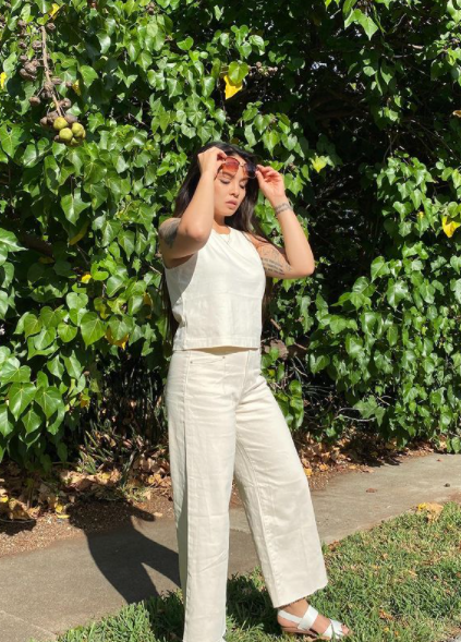 Girl standing, holding glasses up, wearing sleeveless cream top and cream white wide leg jeans