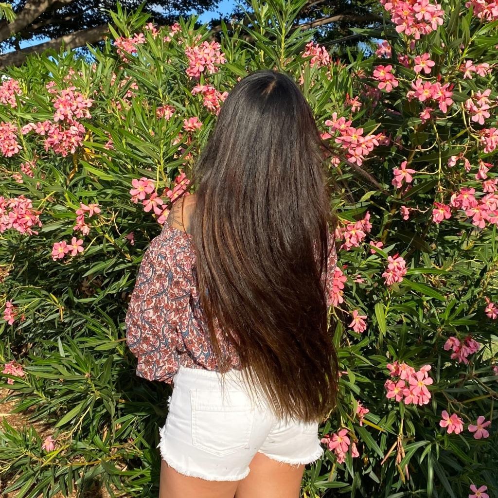 Blogger wearing floral crop blouse and white denim shorts from thredUP